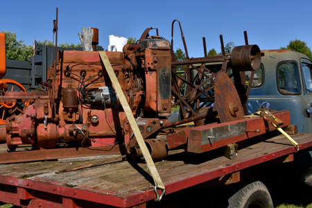 A large old tractor or heavy equipment engine used for powering the saw driven by a belt is loaded in the back of a vintage truck