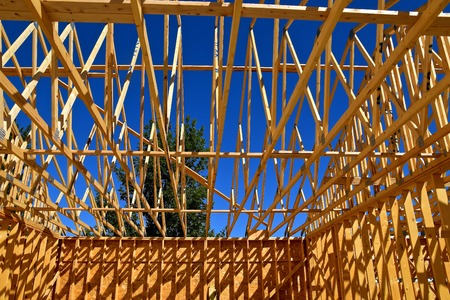 Pre-built rafters on a building project cast their shadows on the walls Stock Photo