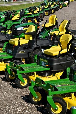 HAWLEY, MINNESOTA, 22 sierpnia 2017: Rząd zielonych i żółtych nowych kosiarek samojezdnych to produkty John Deere Co, amerykańskiej korporacji, która produkuje maszyny rolnicze, budowlane, leśne, silniki Diesla i układy napędowe