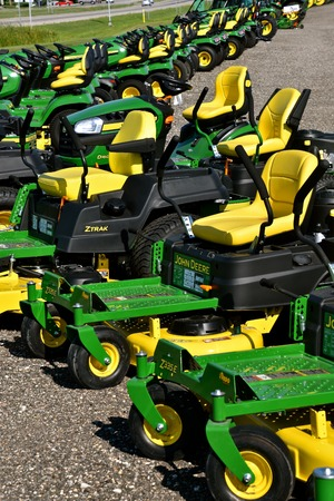 HAWLEY, MINNESOTA, August 22, 2017: A row of green and yellow new riding lawn mower tractors are products of John Deere Co, an American corporation that manufactures agricultural, construction, forestry machinery, diesel engines, and drive trains