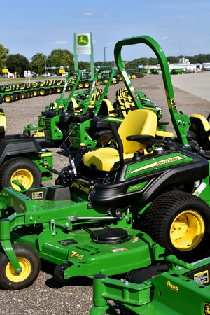 HAWLEY, MINNESOTA, August 22, 2017: A row of green and yellow new riding lawn mower tractors are products of John Deere Co, an American corporation that manufactures agricultural, construction, forestry machinery, diesel engines, and drive trains Publikacyjne