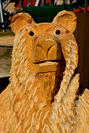 A friendly bear head is being carved with a chain saw from a large log
