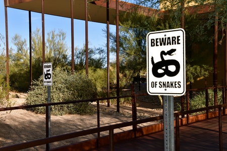 Sign warns  visitors to beware of snakes as they enter a public building. Stockfoto - 100730107