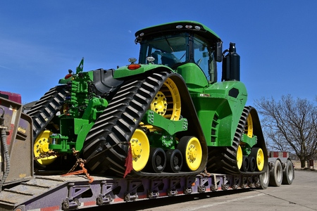 ALEXANDRIA, MINNESOTA, April 22, 2018: The tractor being hauled on a flat bed trailer is a 9620RX, a product of John Deere Co, an American corporation that manufactures agricultural, construction, forestry equipment, machinery, and diesel engines,