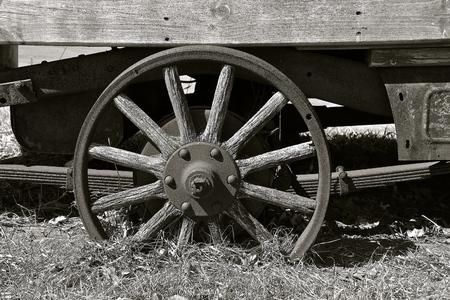 Oud rond houten wiel op een aanhangwagen met spaken. (zwart en wit)