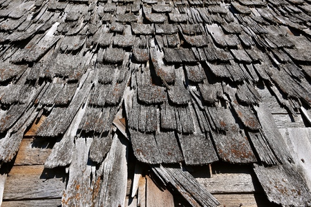 Tattered wood shingles on a decaying outdoor shed