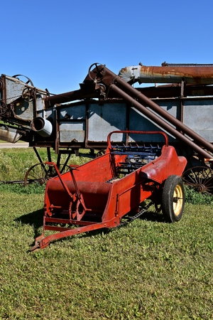 An old manure spreader is parked in from of an even older threshing machine. Stockfoto