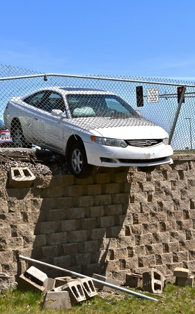 A white car hangs precariously over an embankment after loosing control on a highway.