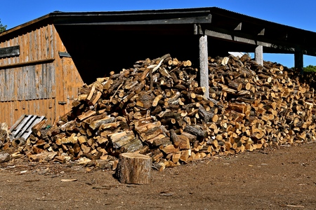 Huge pile of cut and split firewood for steam engines at a threshing bee stored under a shelter.