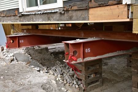 An old house rests on steel girders 65 feet long as a new concrete  basement  and foundation is being created