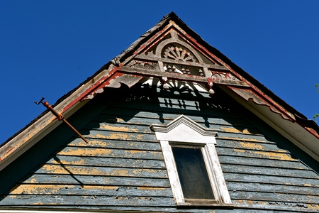 A bar clamp is used to glue a broken facia board on an old house with peeling paint.