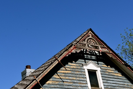 Bar clamps are used to glue a broken facia board on an old house with peeling paint.