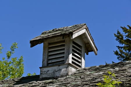 The wood roof and cupola or air vent on a garage building  are in dire need of shingle replacement