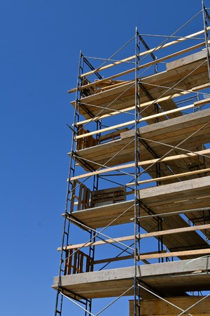 Several layers of scaffolding on a construction site against a bright blue sky. Zdjęcie Seryjne