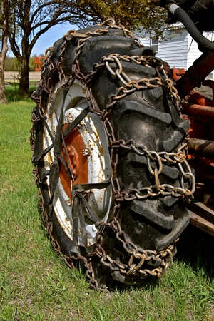 Chains on a tractor tire  for traveling in snow and mud are held on by stretched rubber straps.