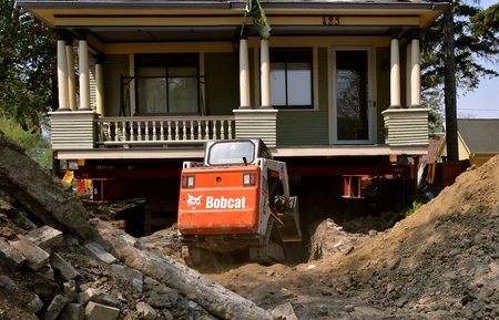FARGO, NORTH DAKOTA, May 14, 2018:  The Bobcat skid steer moving earth from under an old house is headquartered in West Fargo, North Dakota. Foto de archivo - 101998948