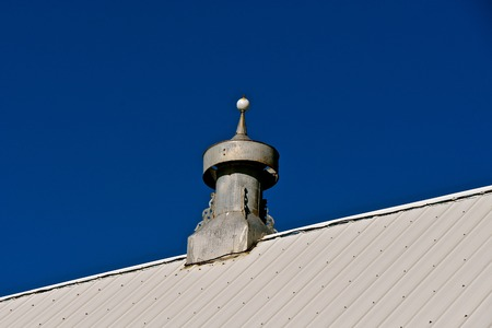 An old cupola on a new metal roofed barn