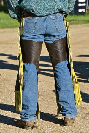 A ranch hand cowboy stands with boots and chaps waiting for a roundup to begin