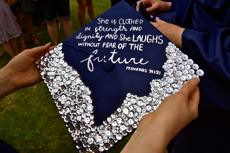 A girl high school student of a private institution holds her graduation cap which is decorated with a bible verse from Proverbs 31:21. Foto de archivo - 102464729