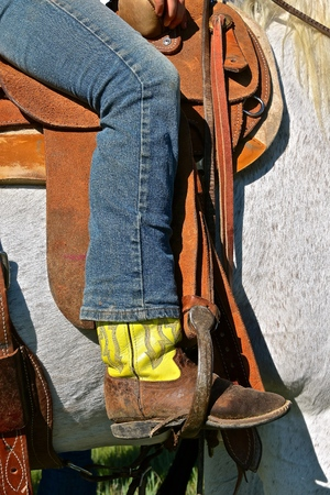 Cowboy  wearing jeans with boot in the stirrup of a saddled horse Stock Photo