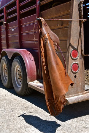 A cowboys pair of chaps are left hanging on the trailer which transports his horse.
