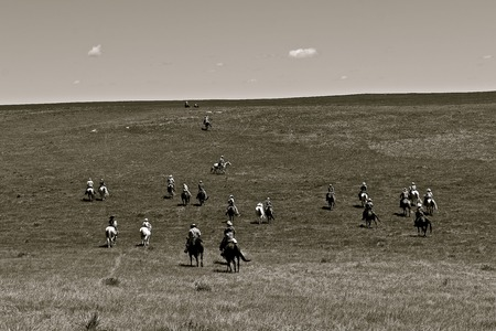 Unidentified cowboys ride over the prairies headed to a roundup and branding session. (black and white)