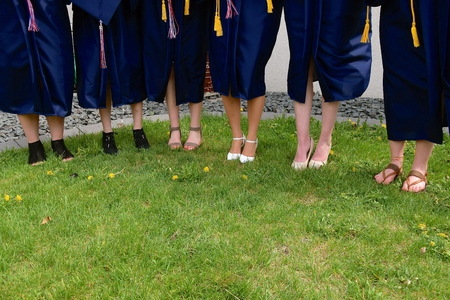 Hight school girls in graduation gowns display a variety of shoe styles.