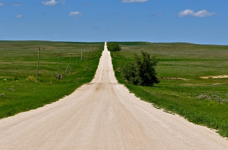 A gravel road in the prairies and rolling plains of South Dakota disappear into the horizon.
