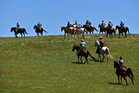 Unidentified cowboys and cowgirls ride horseback over the prairies headed back to the ranch after a roundup and branding session.