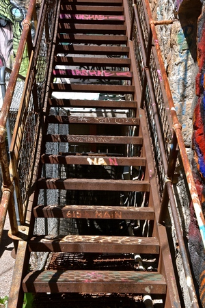 Metal steps in an city alley leading to an apartment are printed with words and graffiti. 스톡 콘텐츠 - 105950477