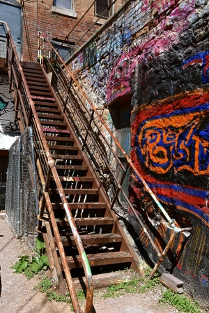 Metal steps in an city alley leading to an apartment are printed with words and graffiti. 스톡 콘텐츠