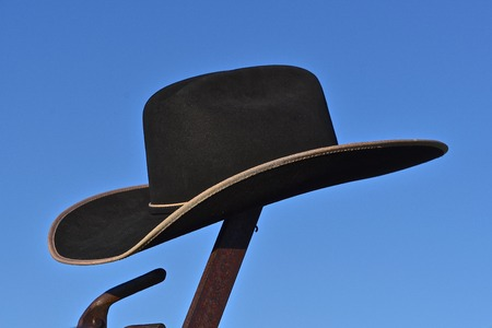 A cowboy has left his hat on top of the handle of an old lever of a machine.
