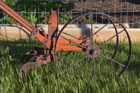 Closeup of the wheel and hoes of an old garden antique weed tiller against a screened in garden Banque d'images