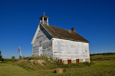 An old rural one room schoolhouse is boarded up and is surrounded by agricultural acres.