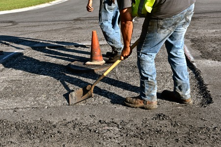 Construction worker blows dirt and waste away from a concrete patch allowing for a new layer of asphalt around a storm sewer cover. Stock Photo