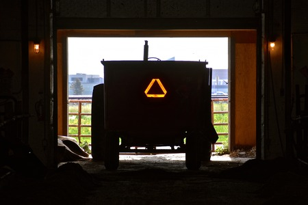 A feed cart backed into a shed displays the Slow Moving Vehicle sign.