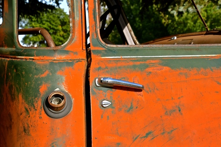 Door and missing gas cap cover of an old late 40s pickup  cab with heavy patina and missing windows