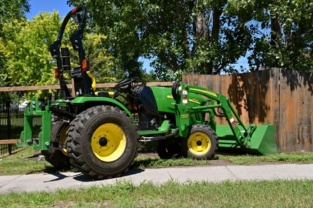 MOORHEAD, MINNESOTA, July 9, 2018: The new 2520 green tractor assisting in fence repair is a product of John Deere Co, an American corporation that manufactures agricultural, construction, forestry machinery, diesel engines, and drivetrains 에디토리얼