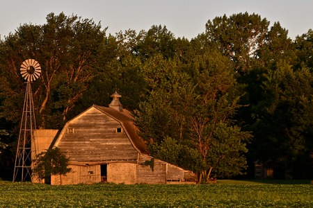The early morning light reflects memories of an old barn, silo, and wind mill. 版權商用圖片