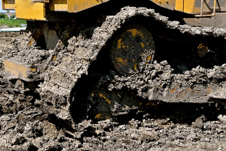 The huge tracks of an excavating  and backhoe machine are caked with mud. Stock Photo