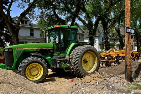 FARGO, NORTH DAKOTA, August 1, 2018:  2017: The John Deere 8400 tractor  digging up a street is a product of John Deere Co, an American corporation that manufactures agricultural, construction, and forestry Editorial