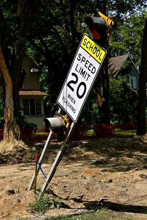 A 20 MPH speed limit school zone sign and warning light stands precariously where a urban street is under road construction. Stock Photo - 110833691