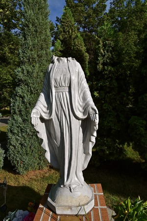 A concrete statue of the Virgin Mary is a victim of vandalism with the decapitation of the head. 스톡 콘텐츠
