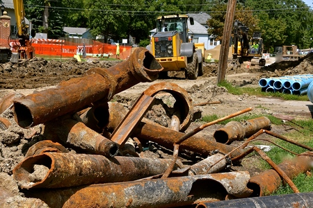Old rusty, cracked sewer and sanitary metal pipe are removed from a street construction project. Imagens