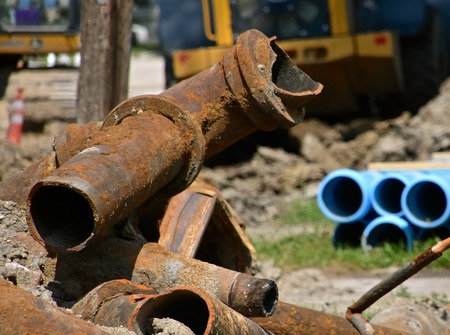 Pile of rusty and mutilated sewage and sanitary metal pipes dug out in a street repair construction scene.