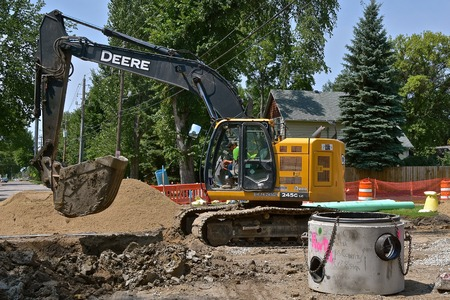 FARGO, NORTH DAKOTA Aug 1, 2018: The excavating machine  245 G used in road construction is a product of John Deere Co, an American corporation that manufactures agricultural, construction, forestry machinery, diesel engines, and drivetrains