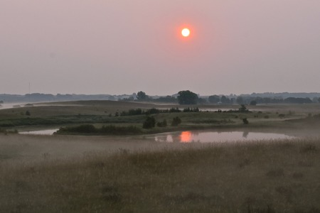 The sunrise to the east is covered with fog and a haze from the smoke of forest fires. Banque d'images - 110833917