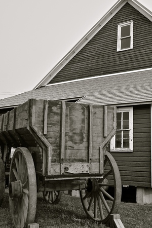 An old grain wagon with wooden wheels is parked in front of a farm granary used to store small grain. Фото со стока
