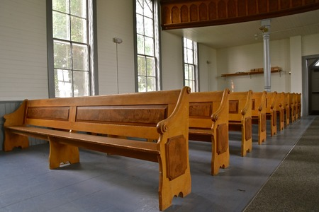 Rows of old wooden pews in a historic Lutheran church Editorial
