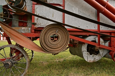 A long leather belt is wound up into a tight roll on an old threshing machine used to harvest small grain. Reklamní fotografie